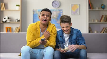 snoepen : African-American and Caucasian friends watching comedy show on TV eating popcorn