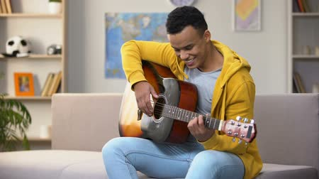 favori : Happy African-American teenager playing guitar, enjoying favorite hobby, leisure