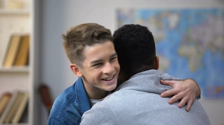 saudação : African-American and European teenage boys hugging, happy to see each other