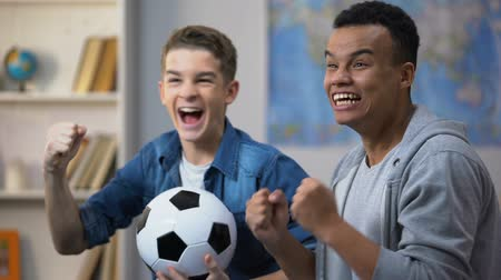 afro amerikan : Emotional multiracial teenage friends cheering for national soccer team, fans Stok Video