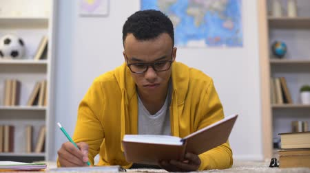 reference : Afro-American student writing essay, preparing for important lectures in college
