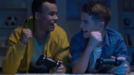 teen age : Emotional multiracial male friends winning computer game, leisure activity