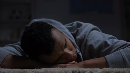 frustração : Unhappy afro-american teenager lying on floor, suffering racial discrimination