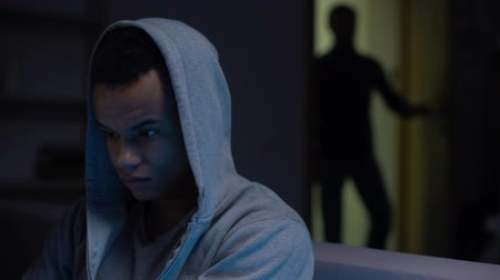 pszichológia : Scared african american teenager sitting in darkness male opening door, violence Stock mozgókép