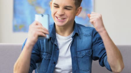 temper : Stressed school boy finally winning in video game on smartphone, leisure time Stock Footage