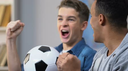 watch tv : Two excited teenagers celebrate goal of favorite team, watch soccer match on tv