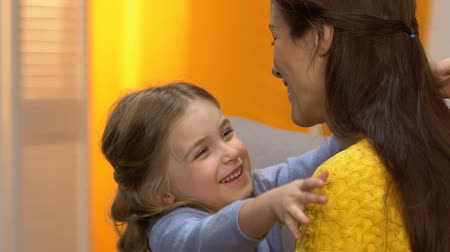 сладость : Sweet preschool laughing girl hugging happy mother, tender relations slow motion