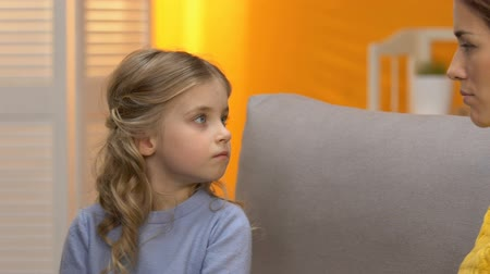 невинный : Sad preschool girl looking at indifferent babysitter, conflict with mom, offence