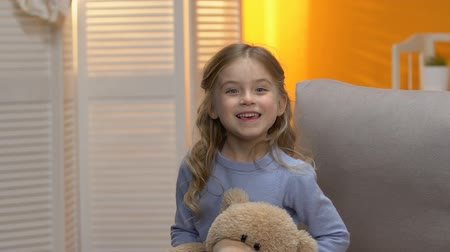 favori : Playful sweet little girl hiding behind plush toy, smiling to camera, happiness Stok Video
