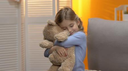 édesség : Sweet curly preschool girl hugging teddy bear and smiling, happy childhood Stock mozgókép