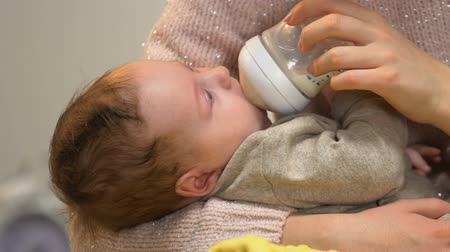 colic : Mommy feeding little cute baby from bottle and holding him in arms tenderly care
