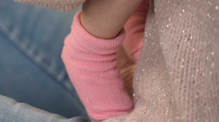 happy socks : Mother holding adorable infant baby girl in pink socks natural clothing for kids Stock Footage