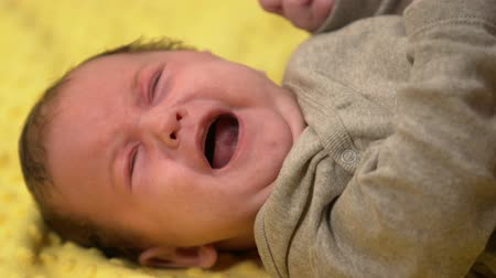 colic : Tiny infant baby lying and crying suffering painful colic, emergence of tooth Stock Footage