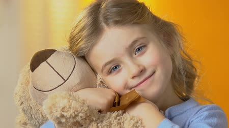 looking : Nice preschool blond girl hugging teddy bear and smiling to camera, happiness