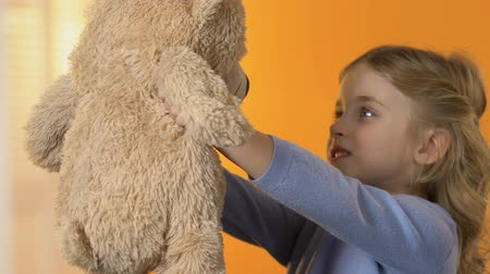 édesség : Adorable preschool girl looking at teddy bear and hugging it favorite toy, child