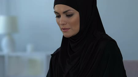 abandonar : Sad arab female in black hijab thinking about life problems, relationship crisis