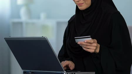 entrando : Smiling muslim female inserting credit card number on laptop, shopping online Archivo de Video