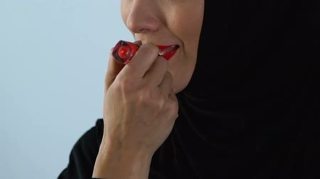 melisa : Arab female in hijab doing bright make-up, applying red lipstick, beauty concept Stok Video