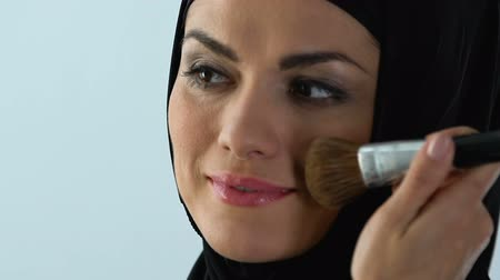 corar : Smiling muslim woman in her 30s applying face blush, anti-age cosmetics, make-up