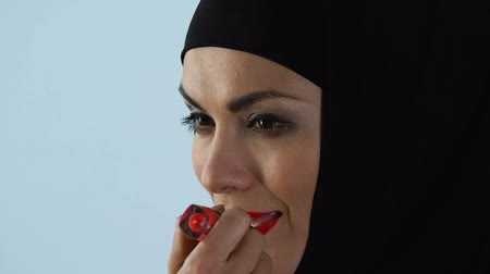 melisa : Confident woman in hijab applying red lipstick in front of mirror, make-up