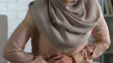 menstruáció : Pretty lady in hijab feeling sharp abdominal pain, premenstrual syndrome, health