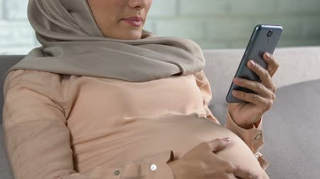 antecipação : Arab pregnant woman scrolling news on smartphone, feeling fatigue, application Vídeos