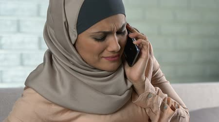 молодые женщины : Troubled pregnant female in hijab calling emergency using phone, contractions