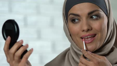 melisa : Pretty muslim woman applying pink lip gloss and smiling in hand mirror, make-up Stok Video