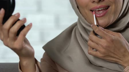 губная помада : Happy lady in hijab correcting make-up, applying lip gloss, preparing for event