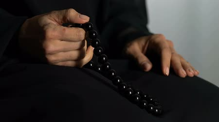 fiel : Faithful muslim woman counting prayers by rosary in hand, religious meditation