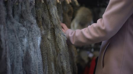traje de passeio : Young female looking at fur coats at street fair, shopping and consumerism