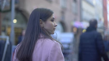choque : Anxious young female walking on crowded street and turning around, paranoia