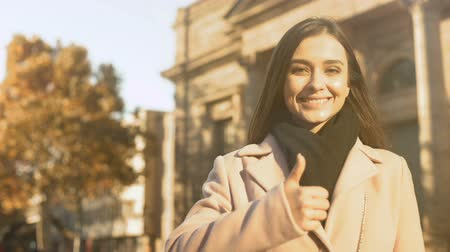 motivováni : Happy motivated female smiling near university building, showing thumbs-up Dostupné videozáznamy