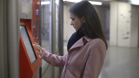ticket machine : Young female tourist buying tickets in self-service terminal, making payment Stock Footage