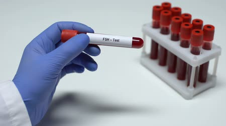stimulating : FSH Test, doctor showing blood sample in tube, lab research, health checkup Stock Footage