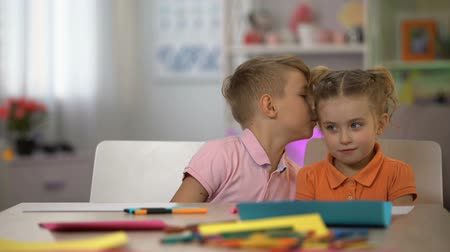 pré escolar : Brother whispering secret sister ear, children communication, bad news, gossips