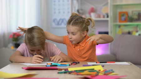 hiány : Cute girl scaring brother studying table, child hyperactivity, attention deficit Stock mozgókép