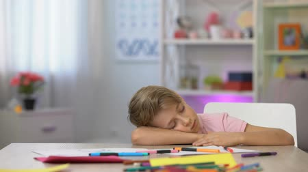 tiredness : Male preschooler sleeping on desk, color pencils and paper on kindergarten table
