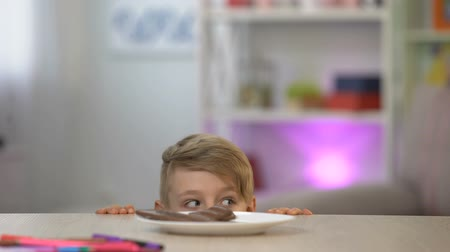 školák : Schoolboy taking secretly chocolate from white plate on table, sweet dessert