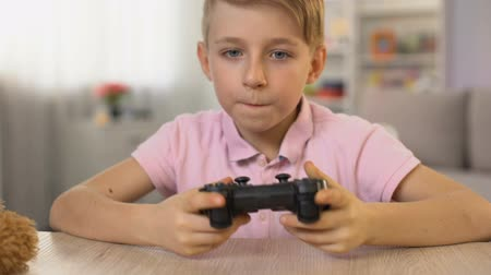 boyhood : Excited male kid taking joystick from table, playing video game, entertainment