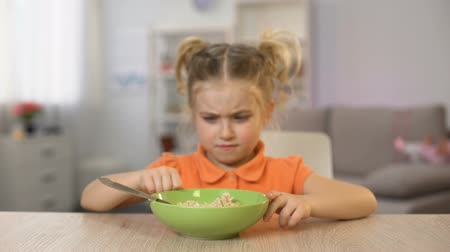 refusing : Girl refusing eat breakfast oatmeal, pushing bowl away, healthy child nutrition Stock Footage