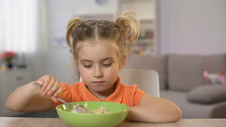 refusing : Mother putting table bowl with healthy oatmeal, daughter refusing eat porridge