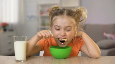 łyżka : Happy little girl eating cornflakes with milk sitting home table, healthy food Wideo