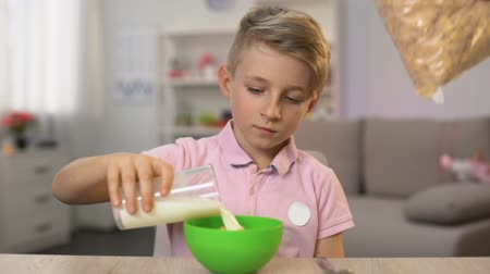 flocos de milho : Schoolboy pouring milk in cereal bowl prepared mother, quick breakfast, health Stock Footage