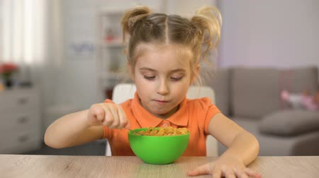 flocos de milho : Hungry female kid eating cornflakes with milk and showing thumbs up, breakfast