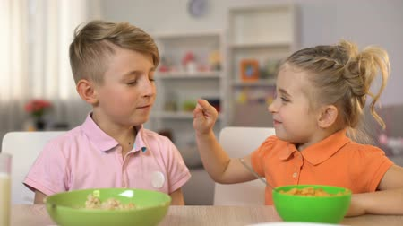 flocos de milho : Playful brother and sister touching nose each other, having fun during breakfast Stock Footage