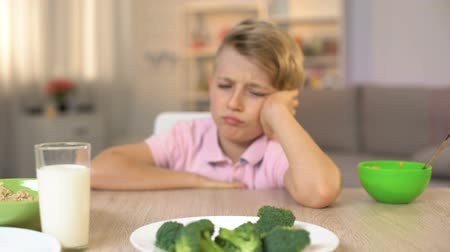 školák : Schoolboy looking sadly at broccoli on white plate, childhood nutrition, food Dostupné videozáznamy