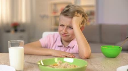 loo : Unhappy boy looking oatmeal with disgust, unappetizing food, healthy breakfast Stock Footage