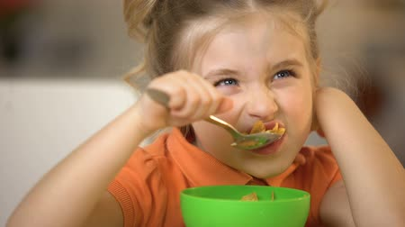 corn flakes : Cute girl eating cereal closeup, appetizing breakfast, morning corn flakes meal