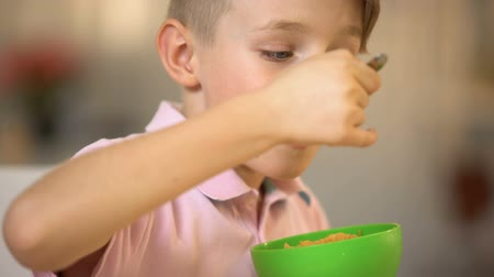 flocos de milho : Satisfied little boy eating cornflakes for breakfast, childhood nutrition, snack Stock Footage